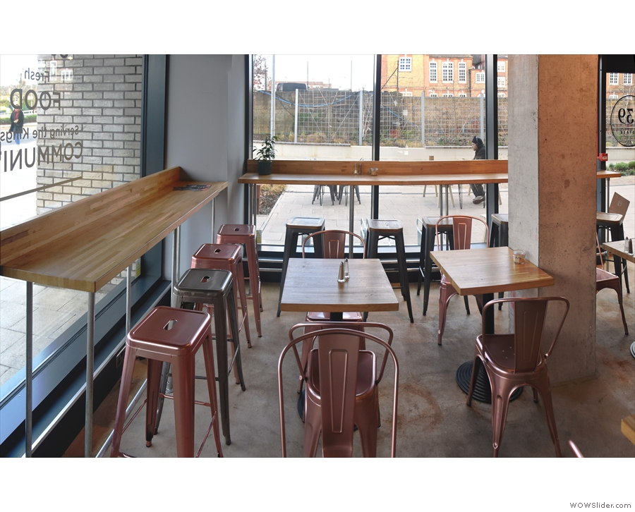 ... while off to the left is another row of tables and a pair of window-bars. The first is at...
