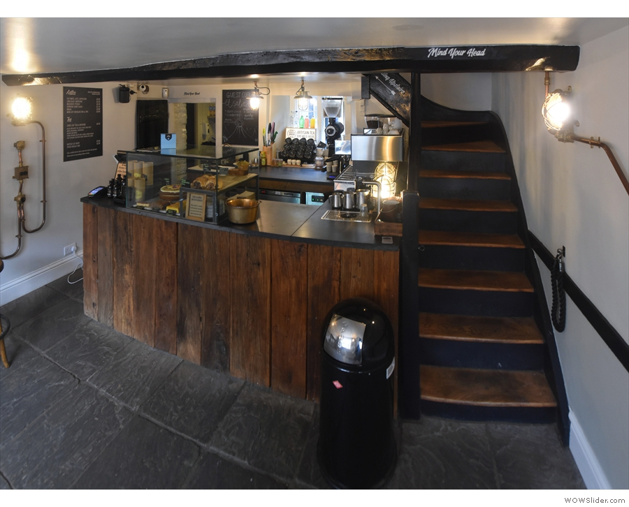 Stepping inside, the counter is at the back of the room, with stairs to the right.