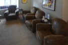 There are two pairs of armchairs, each with a small coffee table, against the left-hand wall.