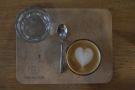 ... in a flat white, served in a glass on a wooden tray, glass of water by the side.