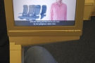 The TV screen lifts out from beneath the seat on an arm to one side.