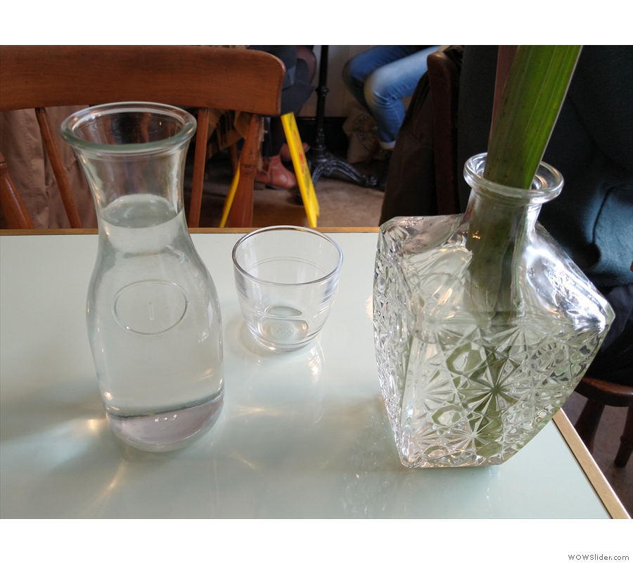 Each table is laid with a carafe of water and some glasses...