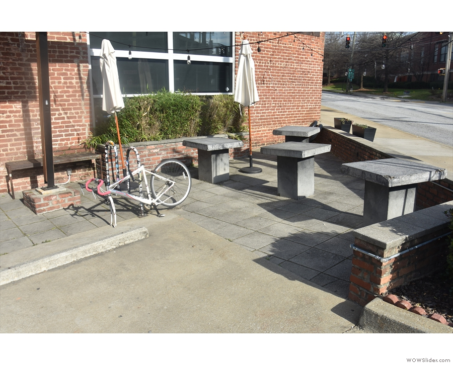 ... and a small, wedge-shaped outdoor seating area with four concrete tables beyond that.