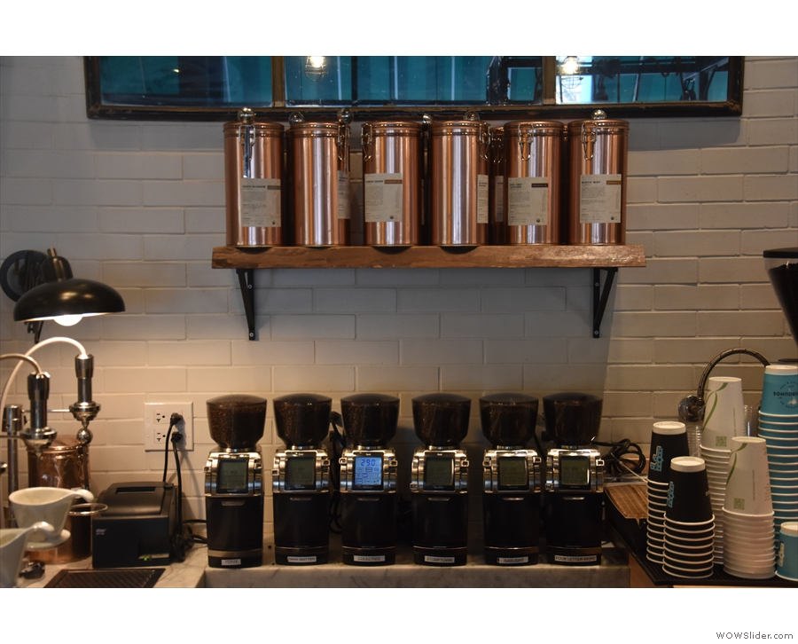 ... with a row of six grinders on the wall behind, one for each brew bar choice.