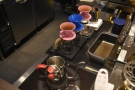 ... and, behind them, a row of Kono pour-over filters, each on their own set of scales.