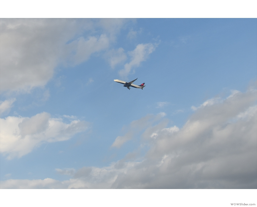 Meanwhile, in the distance, another Delta flight heads into the sky.