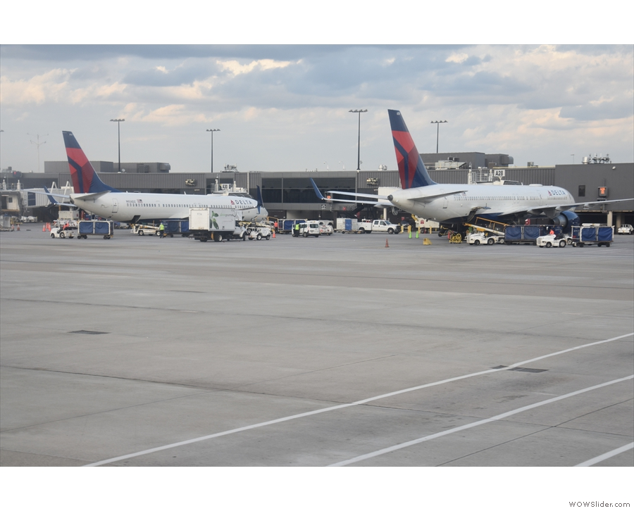 We stand on the tarmac, flanked by Delta planes on the adjacent terminal...