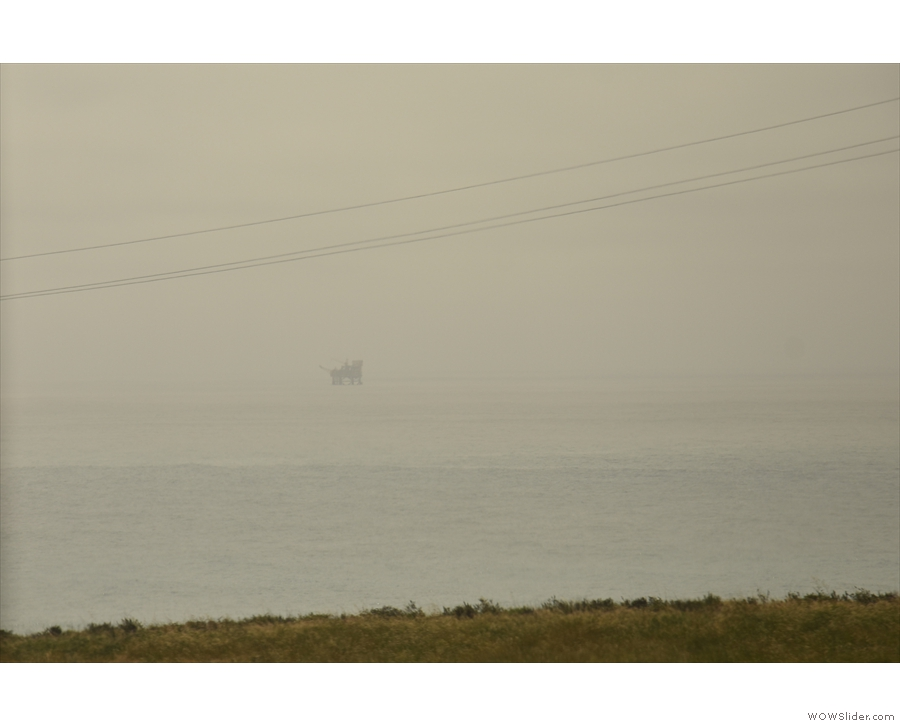 The oil rigs are still out there, partially obscured by the mist.