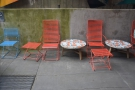 A row of tables/chairs run along the far (left-hand) wall of the outdoor seating area...