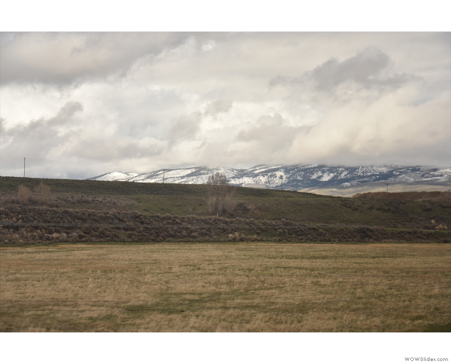... upland meadows, the high, snow-capped peaks of the Rockies in the distance.