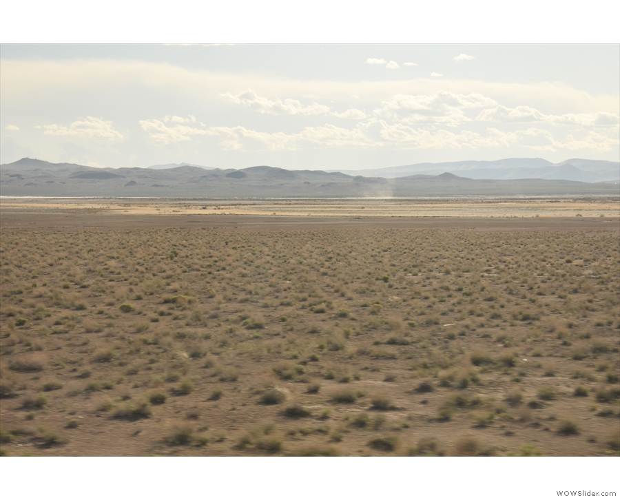 More scrubland, with the distant hills, which start to get closer again.