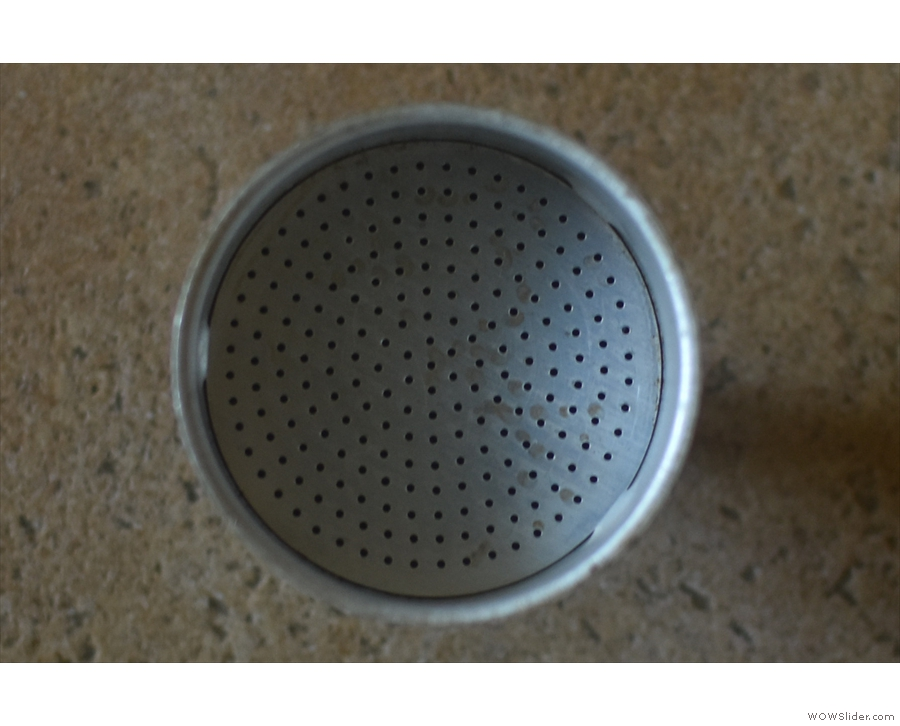 ... through the holes in the bottom of the basket, then through the ground coffee.