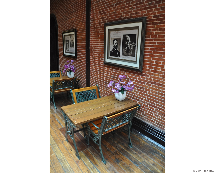 ... down either side of the room against the bare brick walls.