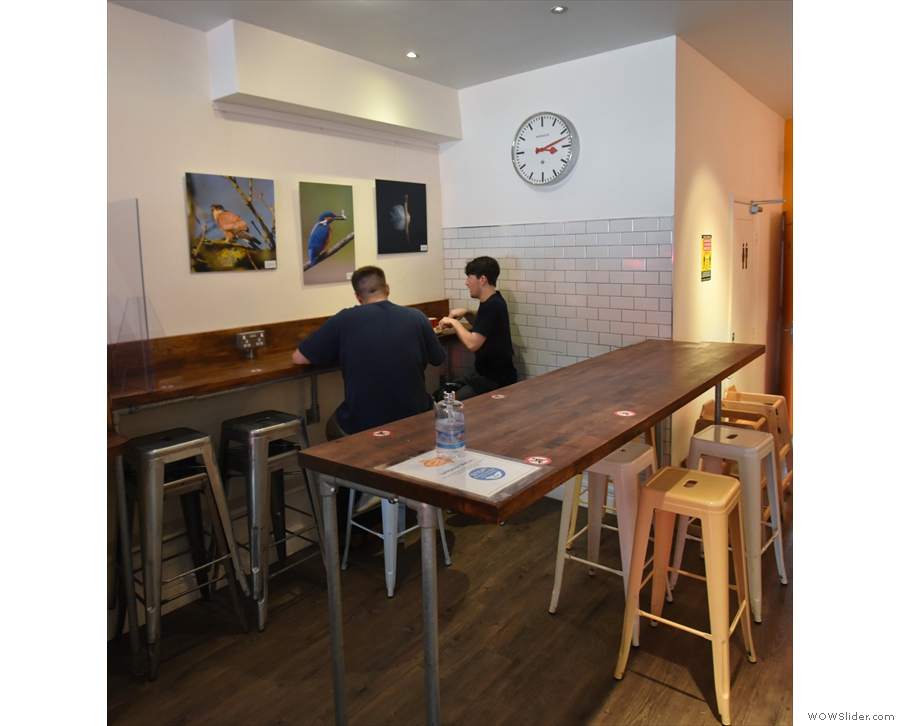 ... with a long, thin table and a bar against the walll on the left-hand side...