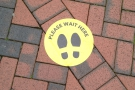 ... where cheery yellow stickers show you where to stand to maintain social distance.
