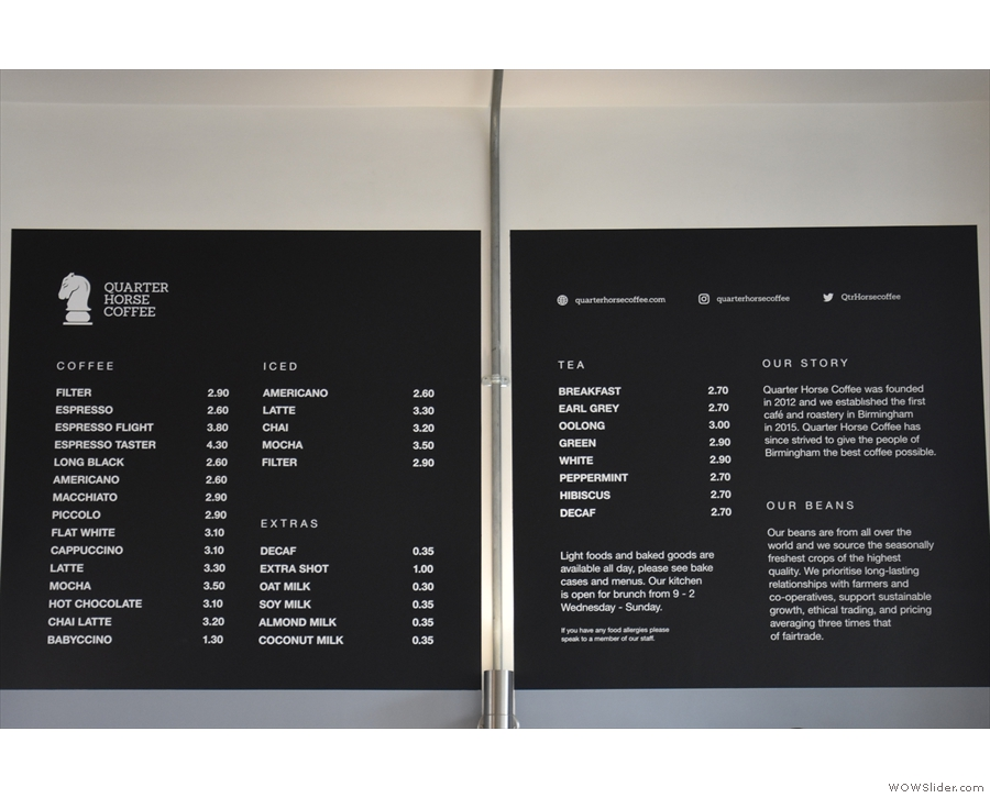 The coffee menu is high up on the wall to the right of the counter, above the retail shelves.