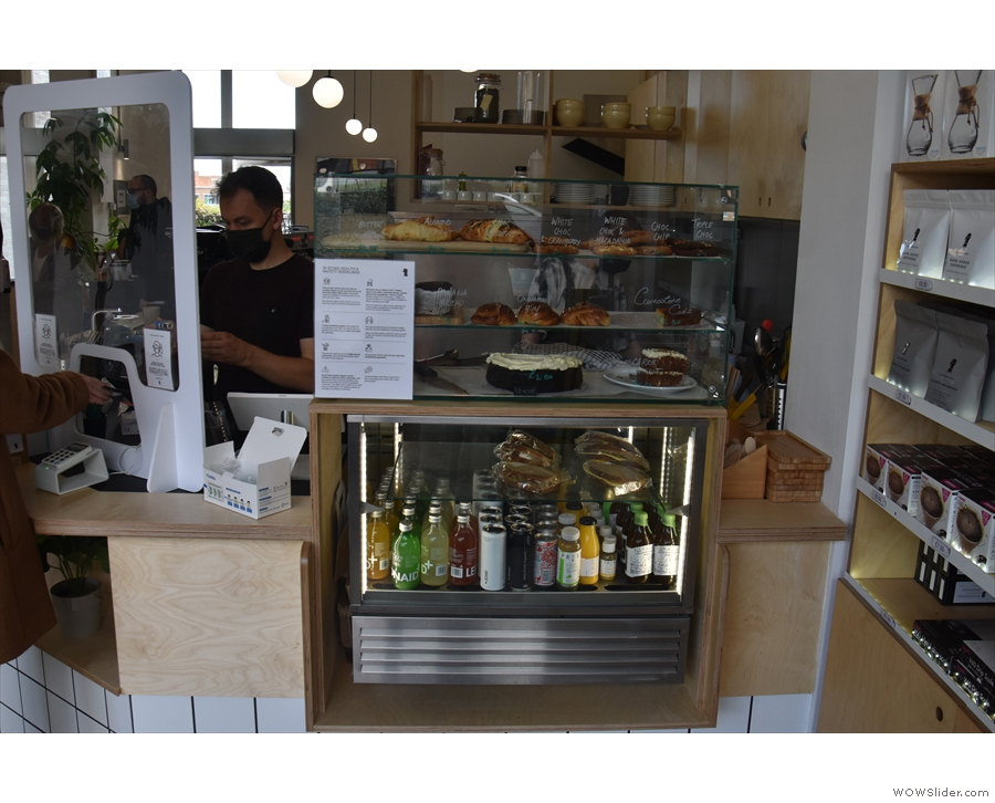 To business. The short side of the counter faces the door, with its display cabinet with...