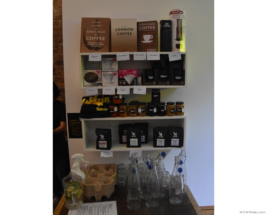 Beyond the counter is a water station with a set of retail shelves on the wall behind.