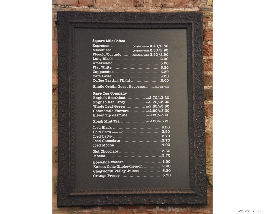 The drinks menu is on the wall behind the espresso machine...