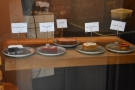 A cake display in the window to your left tempts you while waiting for a member of staff.