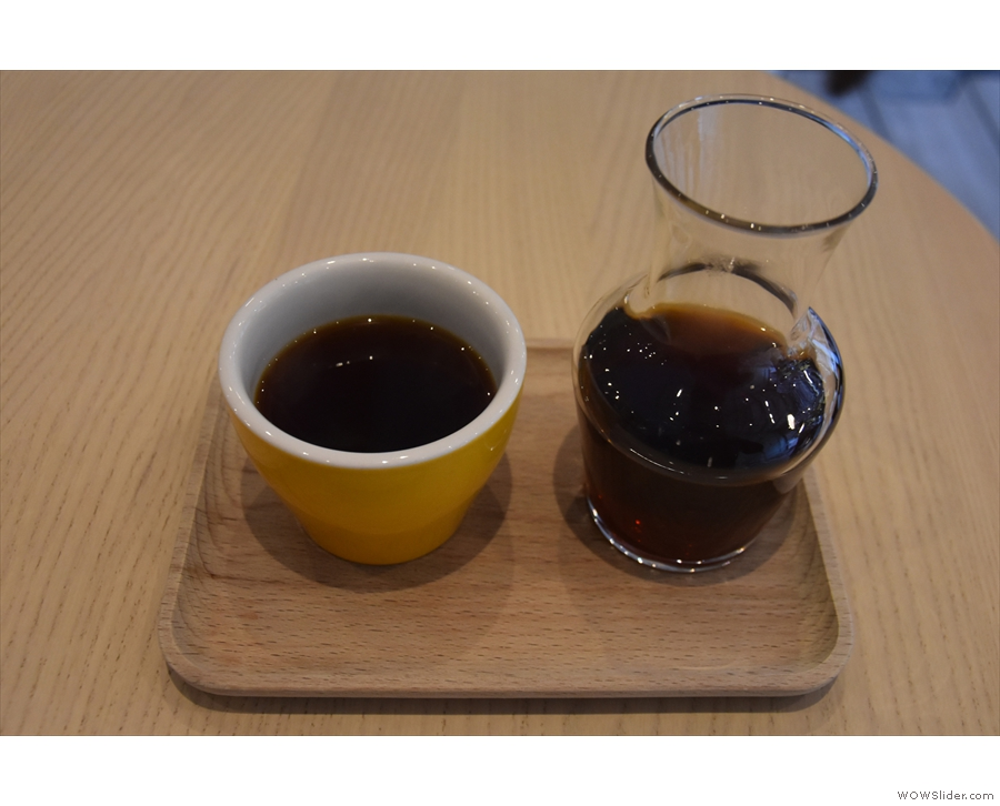 ... served in a carafe and presented on a tray, with a handleless cup on the side.