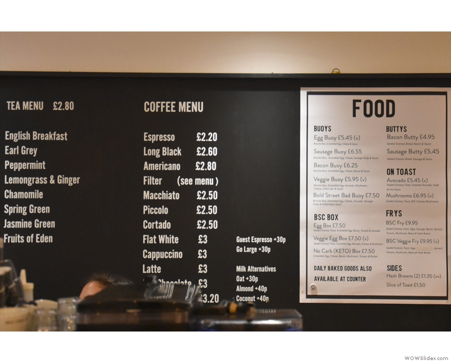The tea, coffee and food menus are displayed on the wall behind the counter...
