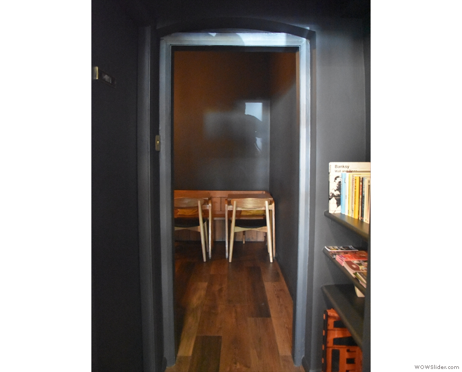 A narrow passage leads past the counter to a door in the back wall...