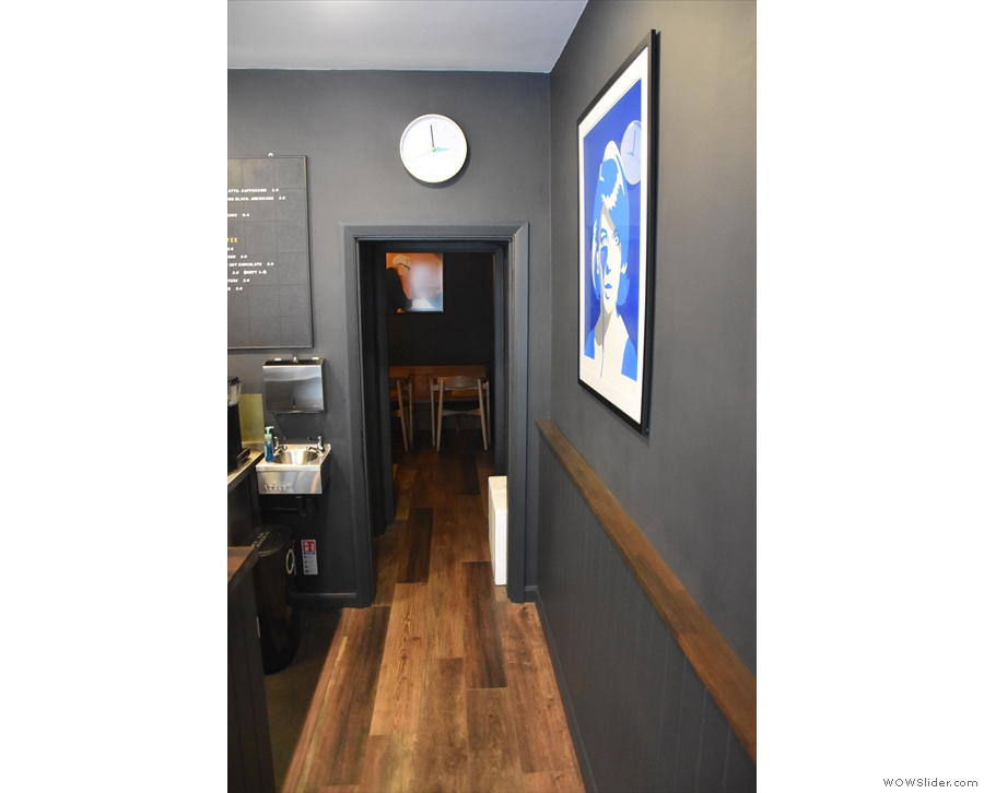 ... at the back? A narrow passage leads past the counter to a door in the back wall...