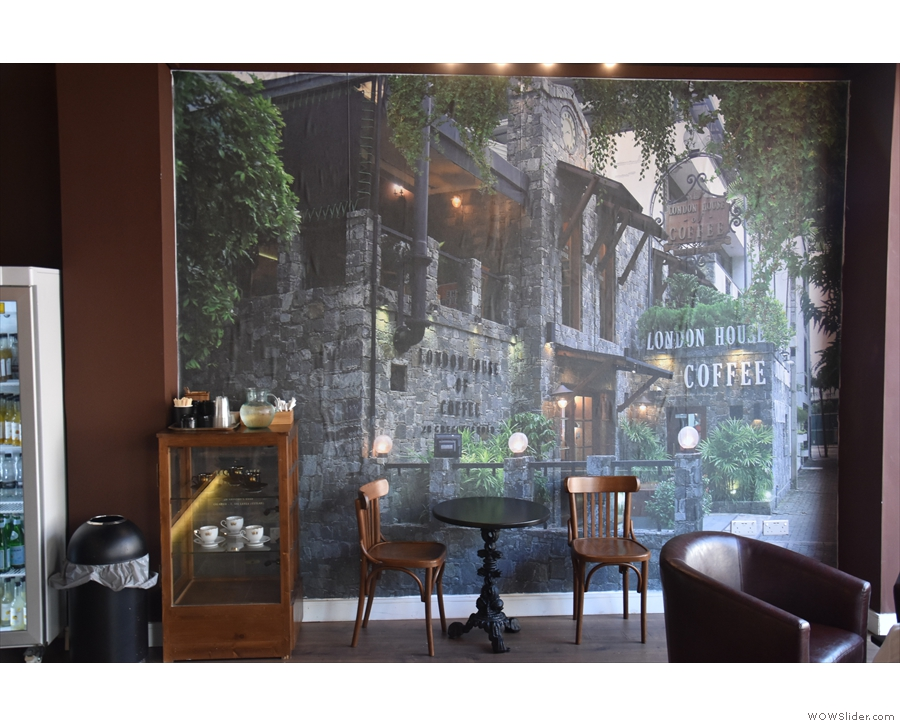 ... a two-person table against the wall, Colombo's London House of Coffee as a backdrop.