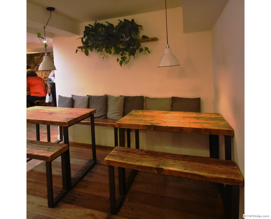 Meanwhile there are these two, four-person tables on the left, against the toilet wall
