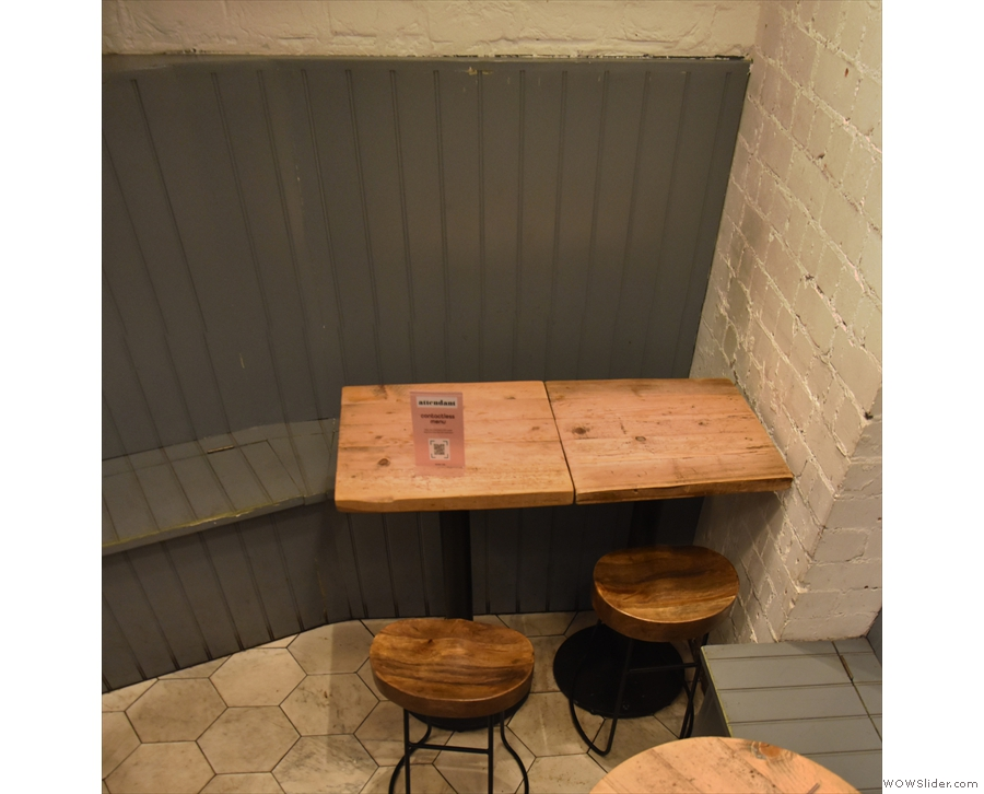 ... before you get to the back wall, there there is a four-person table on the right...