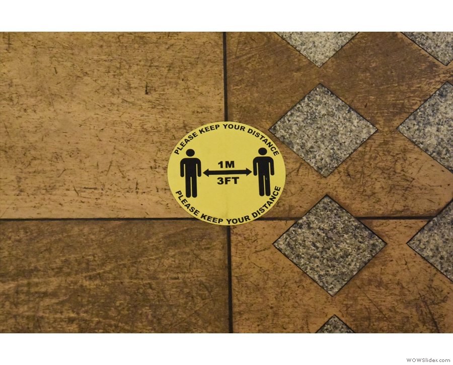 ... while the now familiar signs on the floor help you keep your distance when queuing.