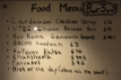 The menus are on the wall behind the counter, with the food on the left...