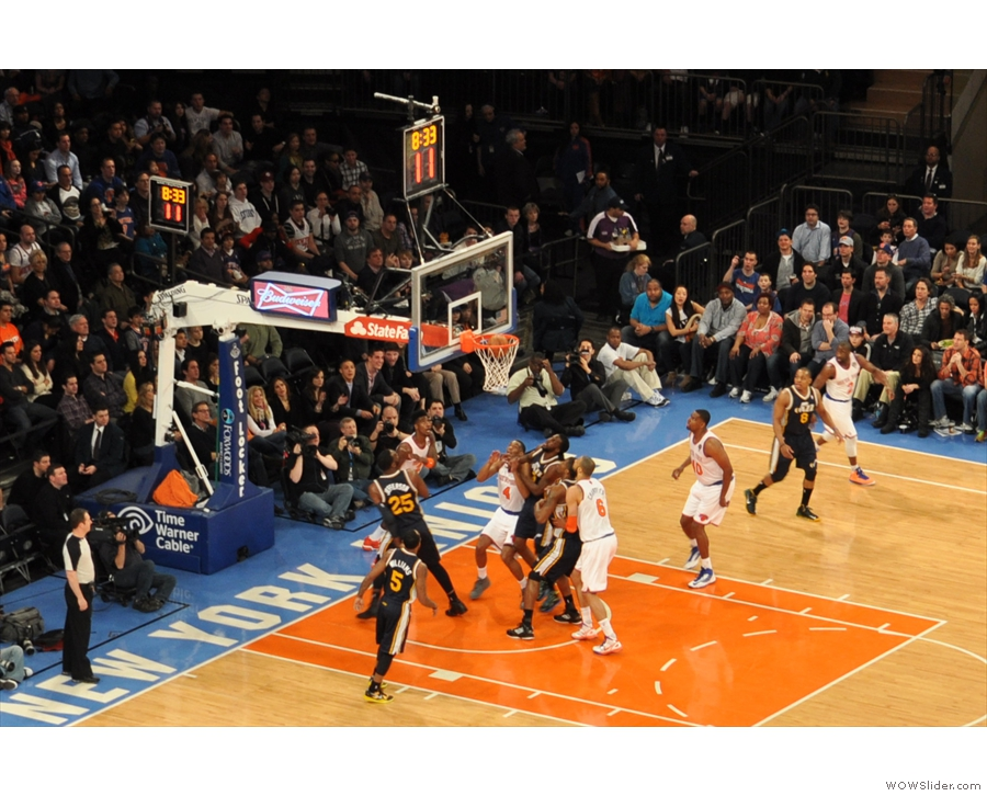 ... of the hometown New York Knicks drives past Al Jefferson of the Utah Jazz to score.