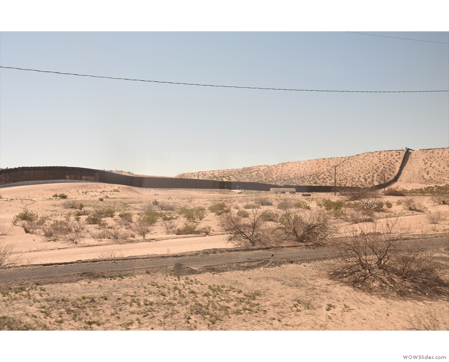 ... although by now the train is in New Mexico. That's the border wall with Mexico.