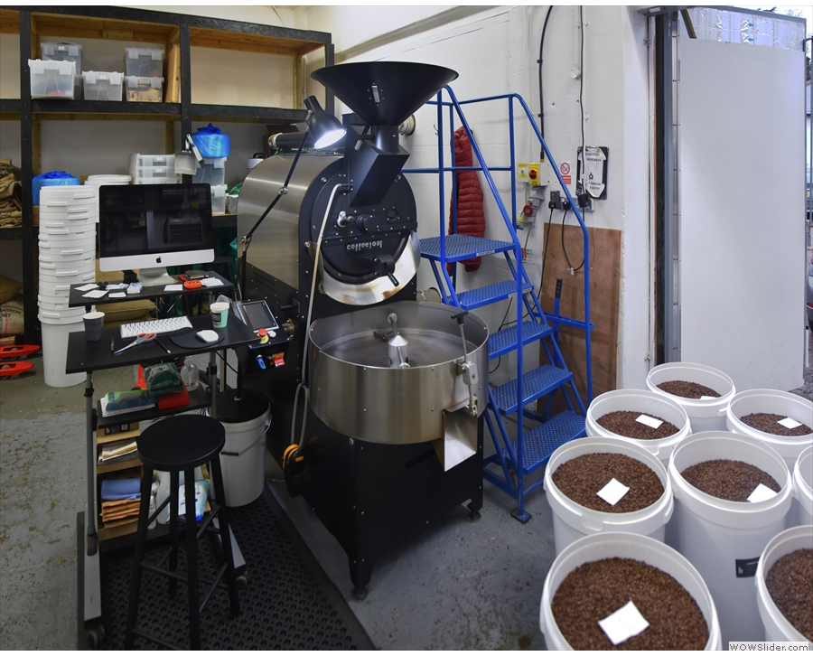 The roaster is run from the control panel on the left, with Cropster on the computer...