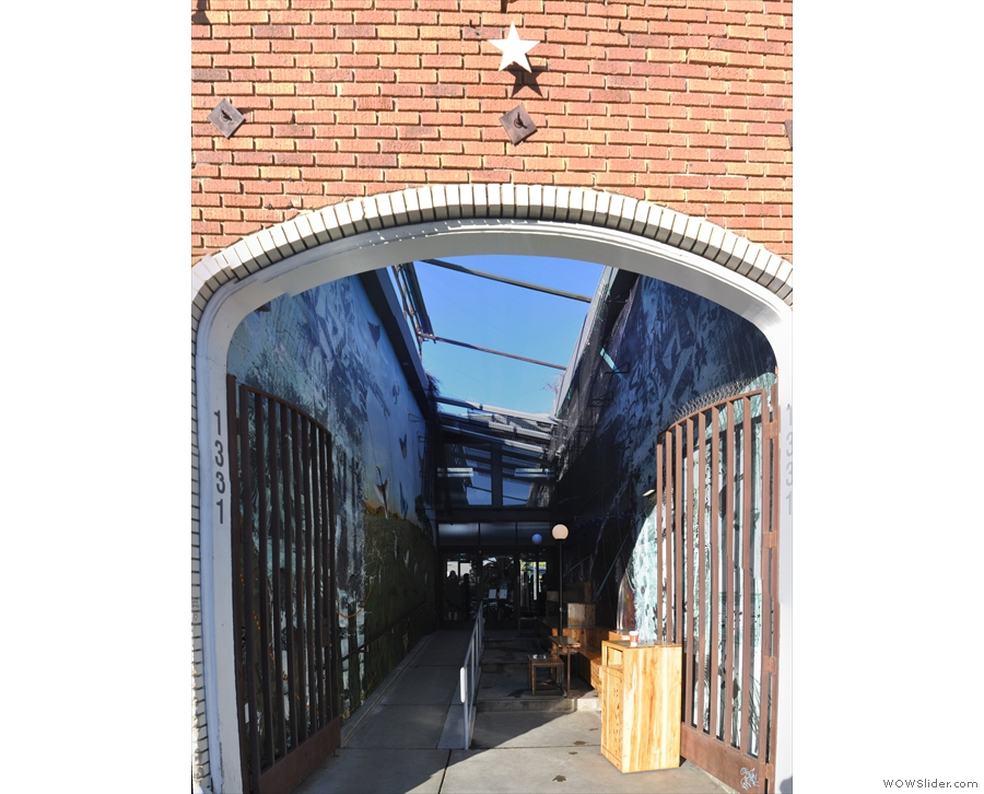 Beyond the arch is a short alley, open to the sky, with Intelligentsia at the far end.