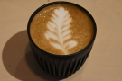 It's still open and serving: here's a flat white I had just before Christmas.