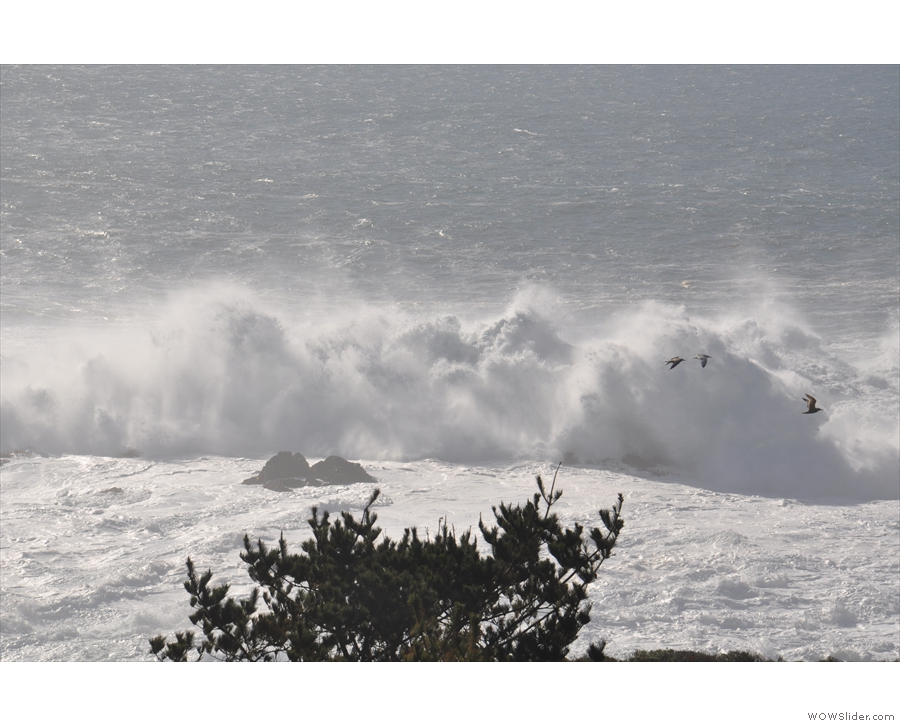 ... as the wave completely engulfs the rocks.