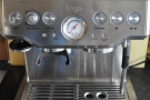 The main controls: power/grinder (left), espresso (right), with a central pressure gauge.
