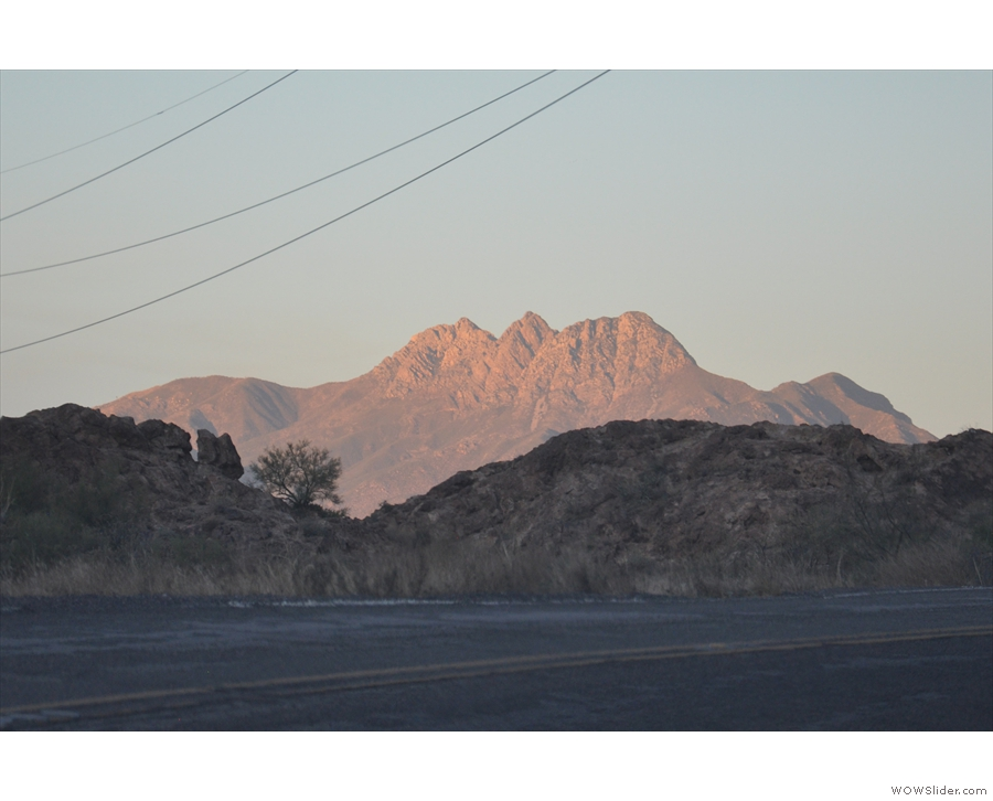 ... was setting, with the road already in shadow and only the tall peaks left in the sun.