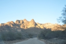 Driving east through a valley on the Apache Trail, the sun setting behind me. The road...