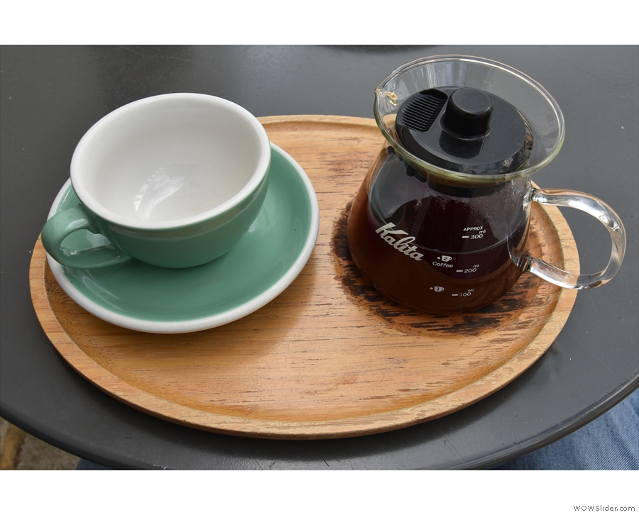 My coffee, served in the carafe, with a cup on the side, all presented on a wooden tray.