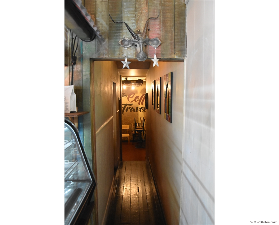 A long, narrow passageway leads along the right-hand wall, past the counter...