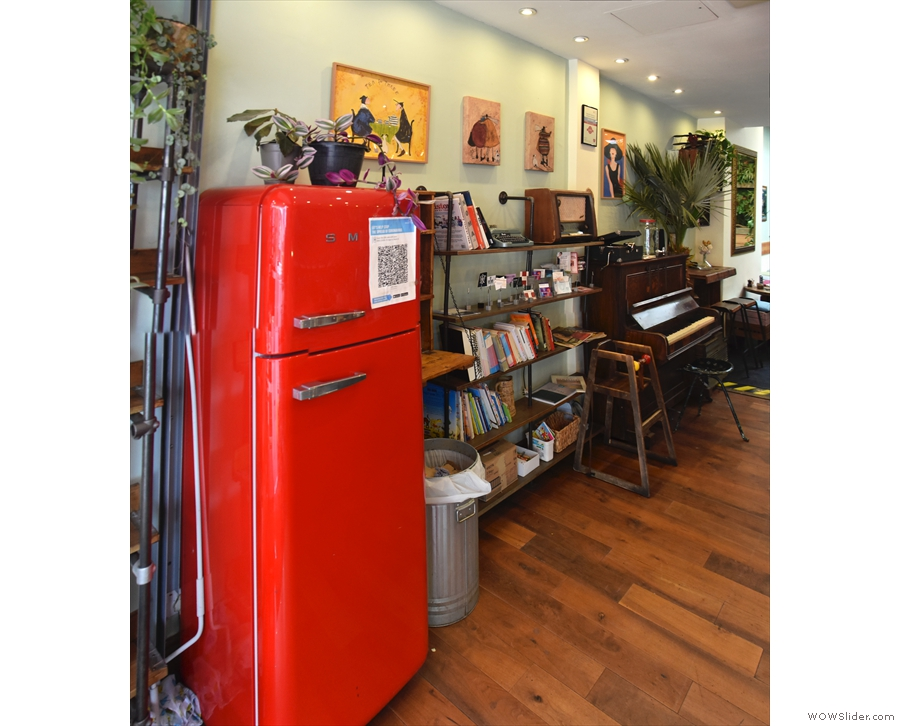 ... after which comes a large, red fridge and an eclectic set of shelves.