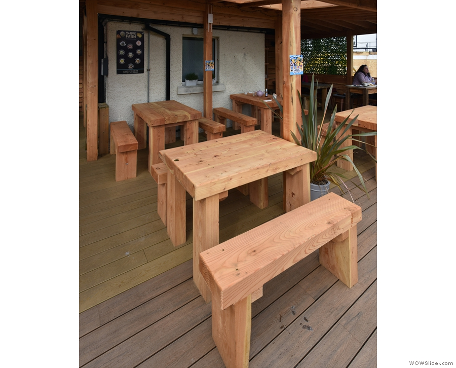 Returning to the decking, there are four of these four-person tables under the roof...