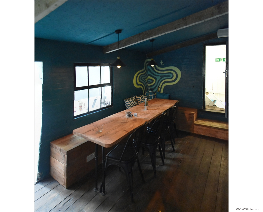 The communal table in more detail. Next to this, an open doorway in the back wall...