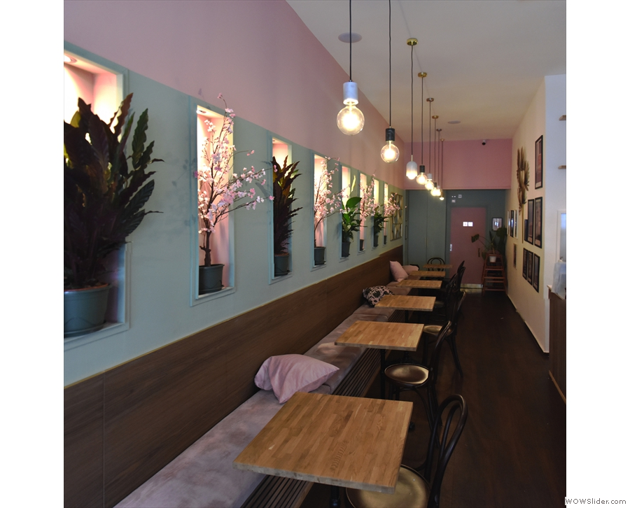 ... the length of the wall, lined by eight two-person tables.