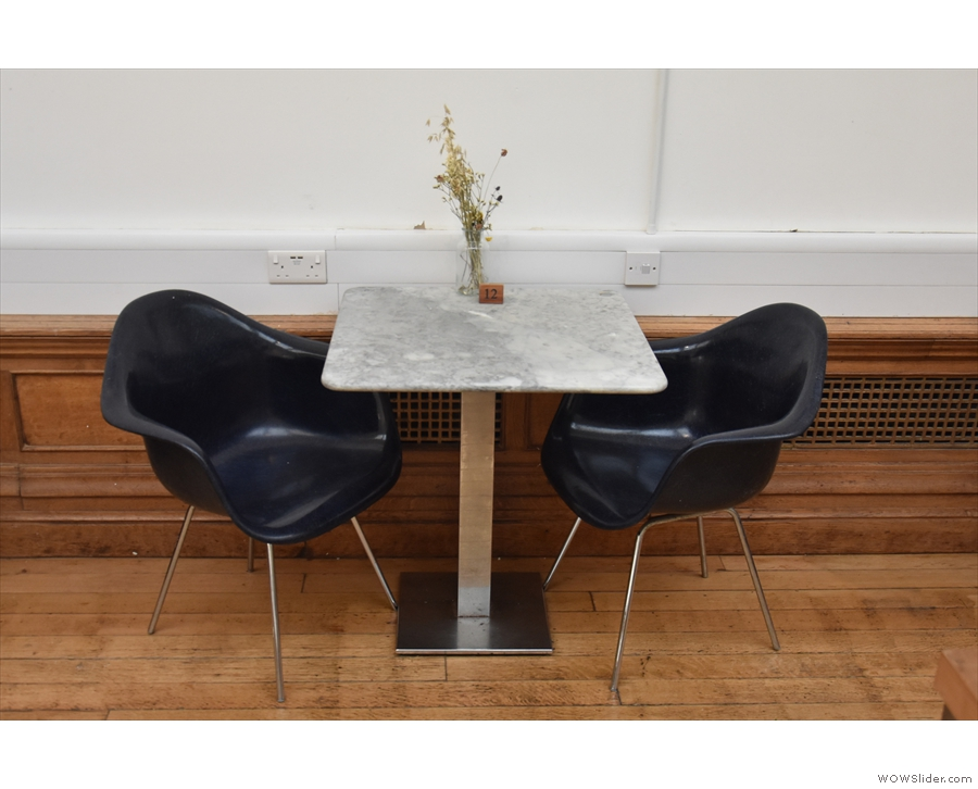 After the sofas comes a pair of two-person tables against the right-hand wall...