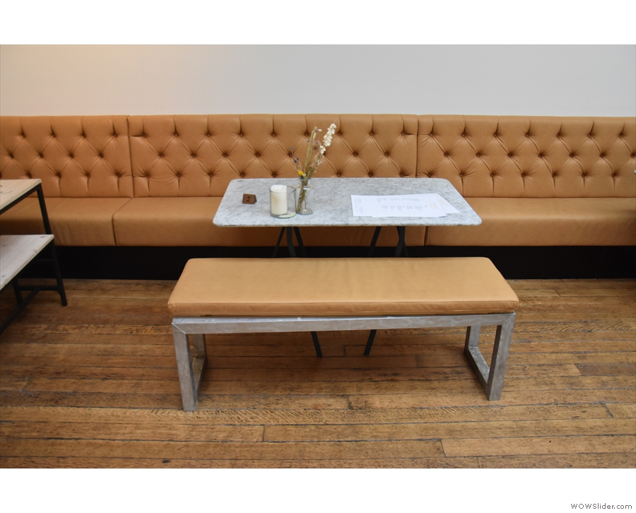 After the long, communal table, a series of smaller, four-person tables run along...